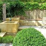 Wasserspiel mit großen Sandsteintrögen. Der aufrecht stehende Eichenpfosten stammt von einem alten Dachgebälk. (Ausführung: Fa. Baum und Garten)