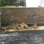 Der leichte Höhenunterschied wird durch die Mauer und das integrierte Wasserspiel schön in Szene gesetzt. (Ausführung: Ralf Ulrich, Der Bewässerungsprofi)