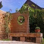 Die rustikale Sitzbank vor dem Sichtschutz wurde aus dem Holz einer Zeder gefertigt, die zuvor im Garten stand. (Ausführung: La vie est verte, FRA)