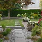 Der Zugang zum Garten erfolgt durch ein Kiesbeet. Die Plattenreihe verbindet die Bereiche und führt auf die Mauer aus Stampfbeton zu. (Ausführung: Fa. Schradi, Rutesheim)