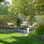 Der lockere Sichtschutz ist mit Rosen, Clematis, Kiwi und Wildem Wein üppig bepflanzt, in den Fugen wächst Thymian. (Ausführung: Fa. Schradi, Rutesheim)