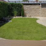 Geschwungene und eingefasste Rasenfläche mittig im Garten, vor die Mauern kommt der große Grill der Familie.