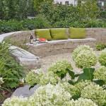 Die Sitzbank wurde in den Schwung der Mauer integriert. Die helle Bepflanzung passt sich dem Farbton der Jurakalk-Mauer an. (Ausführung: Fa. Ralf Ulrich, Weissach)
