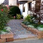 Der Vorgarten wurde mit einem großzügig angelegten Zugang und Trockenmauern umgestaltet, die verbleibenden Pflanzflächen abwechslungsreich bepflanzt. (Ausführung: Fa. Ralf Ulrich, Weissach)